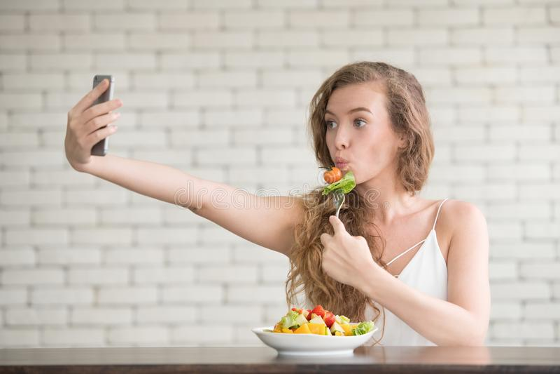 Junge Frau in den frohen Lagen mit Salatschüssel auf der Seite stockbild