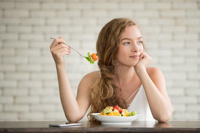 Junge Frau in den frohen Lagen mit Salatschüssel auf der Seite lizenzfreies stockbild