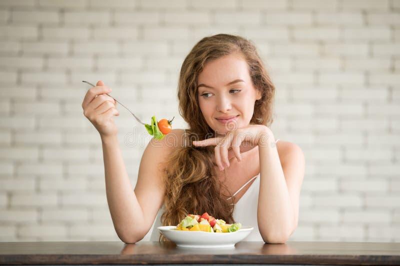 Junge Frau in den frohen Lagen mit Salatschüssel auf der Seite lizenzfreies stockfoto