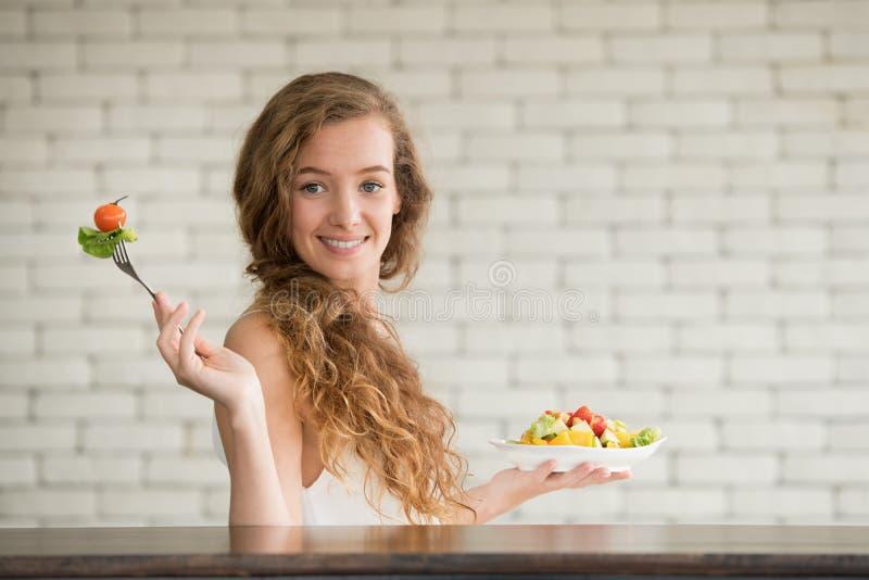 Junge Frau in den frohen Lagen mit Salatschüssel auf der Seite lizenzfreie stockfotografie