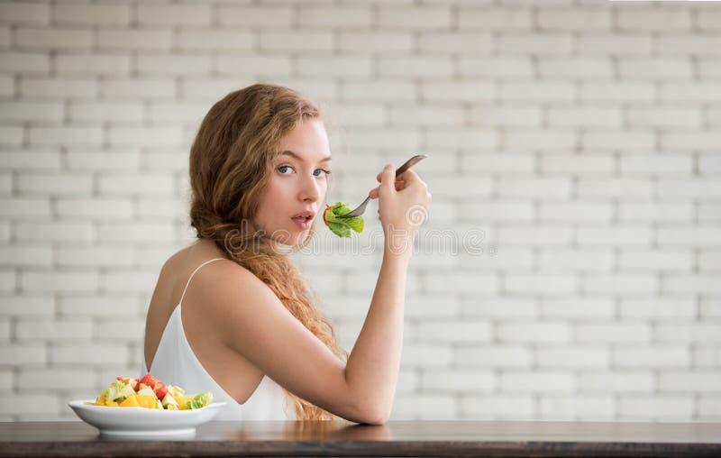 Junge Frau in den frohen Lagen mit Salatschüssel auf der Seite lizenzfreie stockfotos