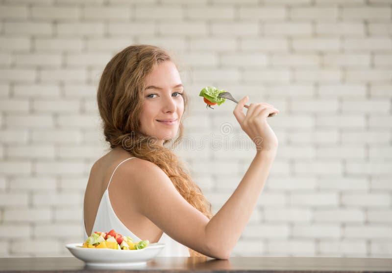 Junge Frau in den frohen Lagen mit Salatschüssel auf der Seite stockfotografie