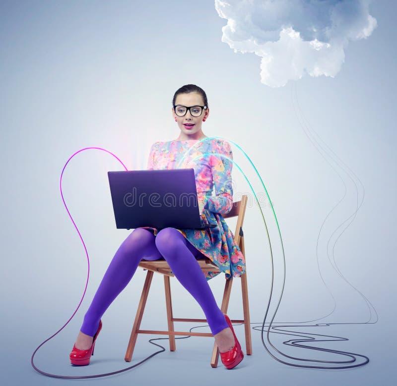 Junge Frau in den Gläsern, die auf einem Stuhl mit einem Laptop sitzen Konzeptwolkendatenverarbeitung lizenzfreie stockfotos