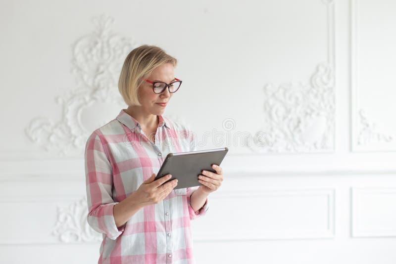 Junge Frau in den Gläsern liest Text auf ihrer Tablette stockbilder