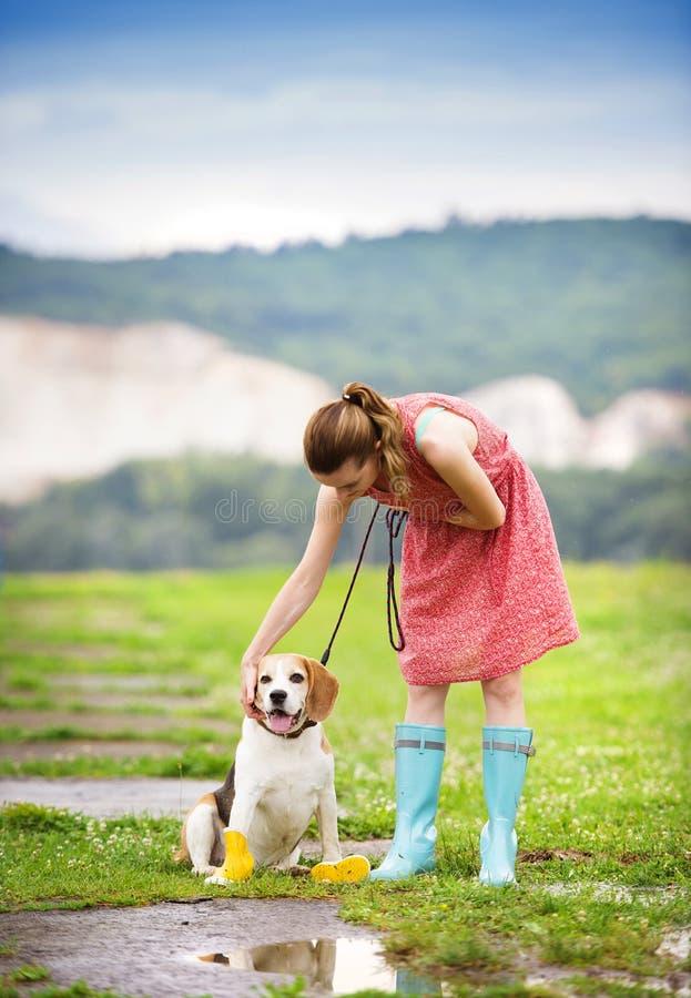 Junge Frau in den Gummistiefeln gehen ihr Hund lizenzfreie stockfotos
