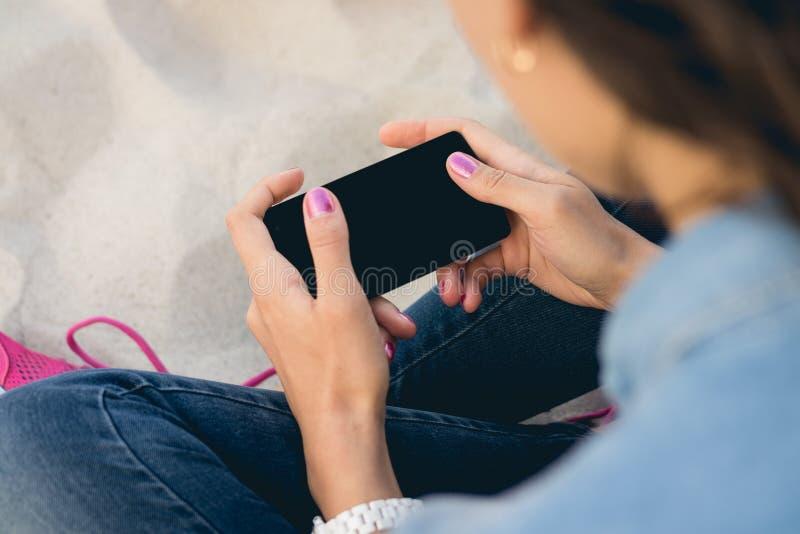 Junge Frau in den Jeans, die auf dem Sand sitzen und einen Handy verwenden stockfotos