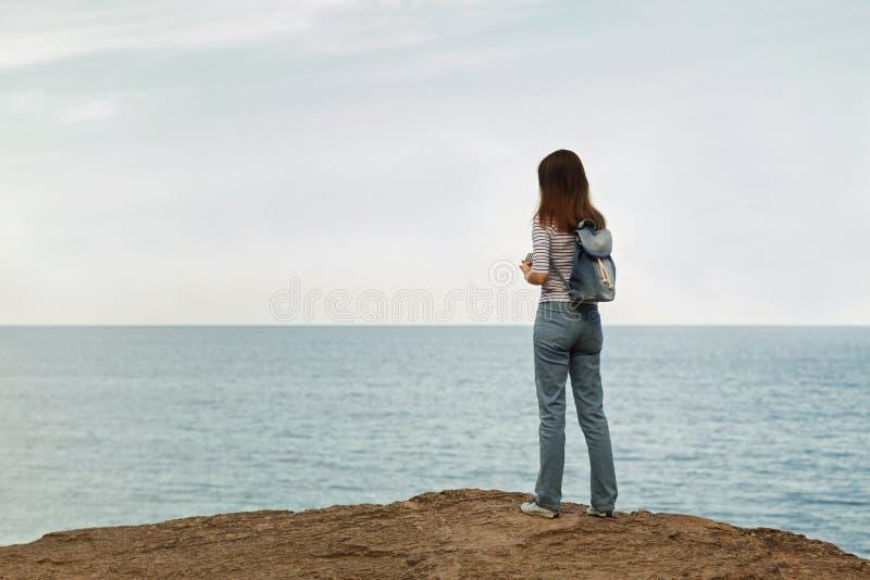 Junge Frau in den Jeans, in gestreifter Spitze und in Turnschuhen auf dem Strand b stockfotografie
