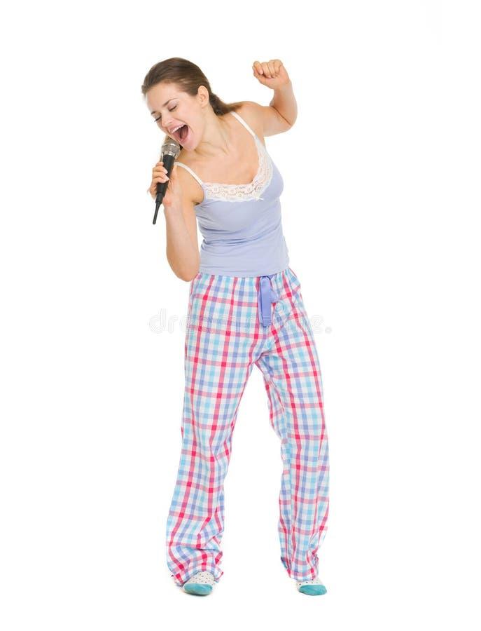 Junge Frau in den Pyjamas singend im Mikrofon lizenzfreie stockfotografie