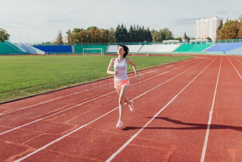 Junge Frau in den rosa kurzen Hosen und Behälter zum Laufen während des sonnigen Morgens auf Stadionsbahn lizenzfreie stockfotografie