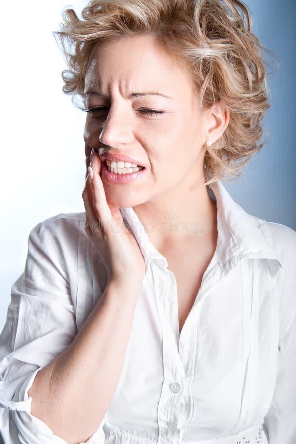Junge Frau in den Schmerz hat Zahnschmerzen lizenzfreie stockfotografie