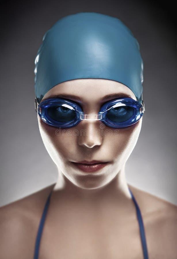 Junge Frau in den Schutzbrillen und in der Schwimmenschutzkappe lizenzfreies stockbild