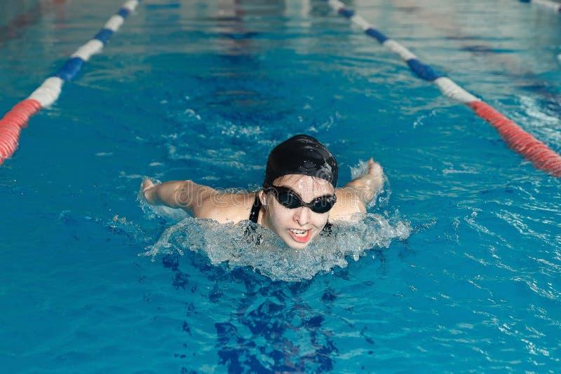 Junge Frau in den Schutzbrillen und Kappenschwimmen-Schmetterlingsanschlagart im Innenpool des blauen Wassers renn lizenzfreie stockfotografie
