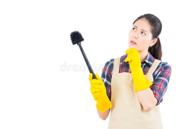 Junge Frau denken Idee, Toilette zu säubern stockbild