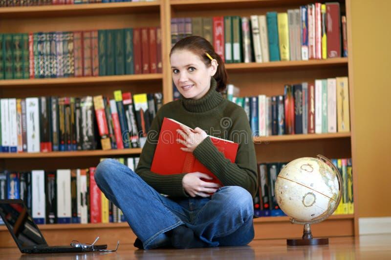 Junge Frau in der Bibliothek lizenzfreies stockbild