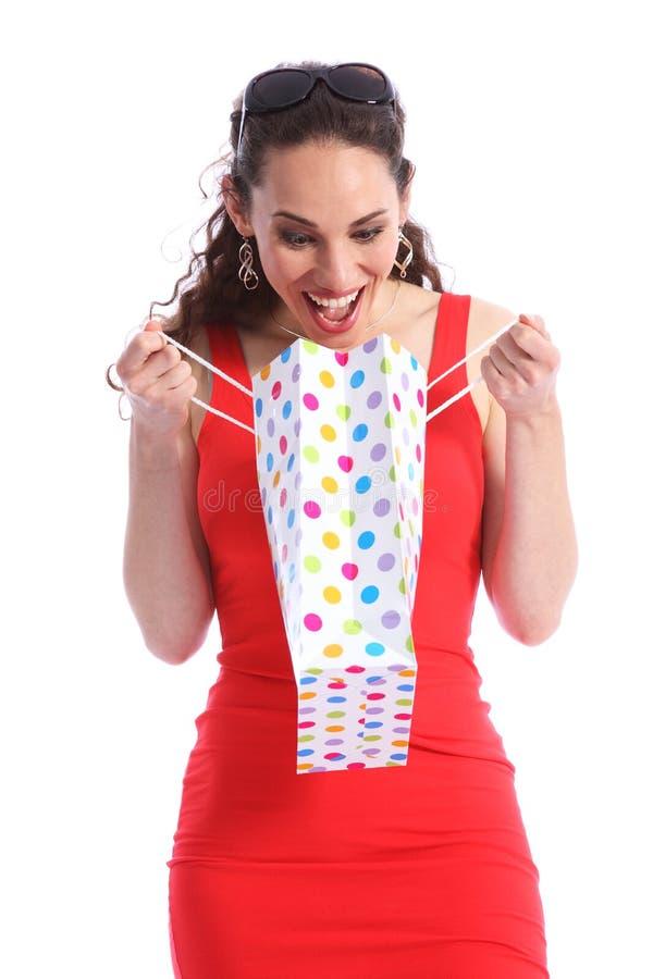 Junge Frau der glücklichen Überraschung öffnet Einkaufengeschenkbeutel stockfotos