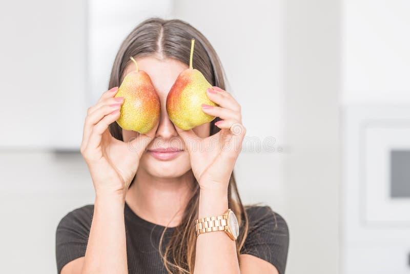 Junge Frau in der Hauptküche, die über zwei Birnen schaut stockbilder