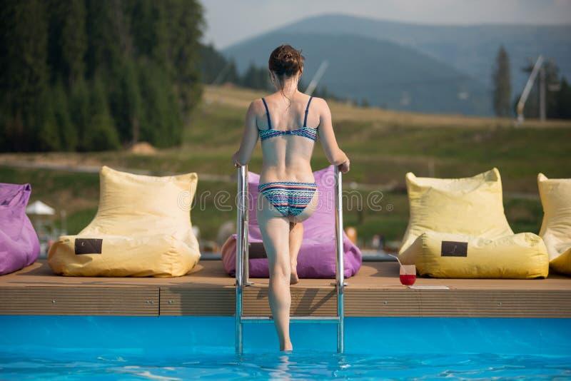 Junge Frau der hinteren Ansicht, die vom Wasser eines Swimmingpools am Erholungsort, nahe Ständen ein Glas mit einem Getränk hera lizenzfreies stockfoto