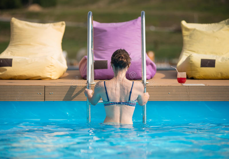 Junge Frau der hinteren Ansicht im Badeanzug, der vom Wasser eines Swimmingpools am Erholungsort herauskommt lizenzfreies stockbild