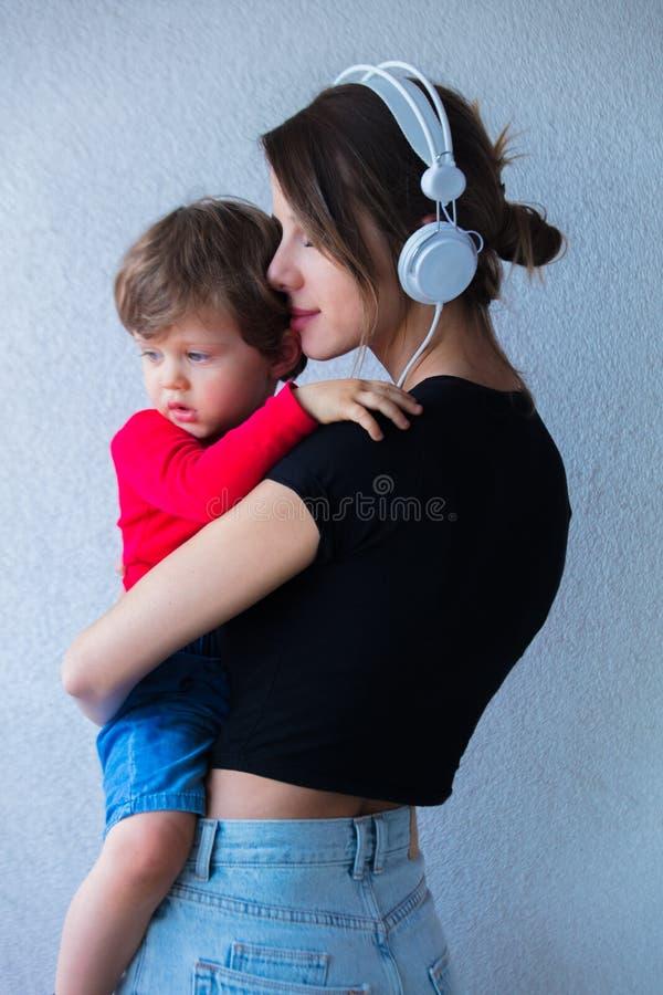Junge Frau in der Hut- und Art90s Kleidung und im kleinen Kleinkindjungen lizenzfreie stockfotografie