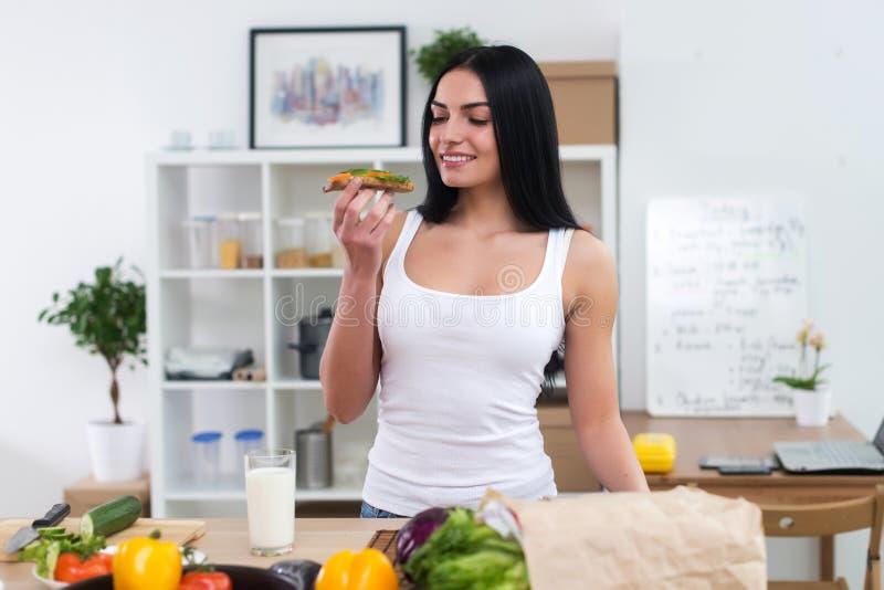 Junge Frau in der Küche, die gesundes, gesundes Sandwich mit Gemüse und Glas der Milchfront essend frühstückt stockbild
