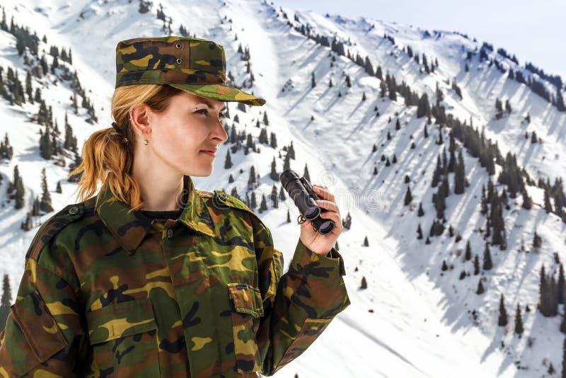 Junge Frau in der kakifarbigen Uniform mit Ferngläsern stockfotos