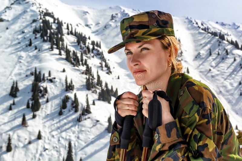 Junge Frau in der kakifarbigen Uniform mit Spazierstöcken auf einem Hintergrund von Schnee-mit einer Kappe bedeckten Bergen stockfotos