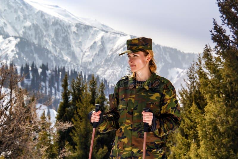 junge Frau in der kakifarbigen Uniform mit Spazierstöcken in den Bergen stockfotografie