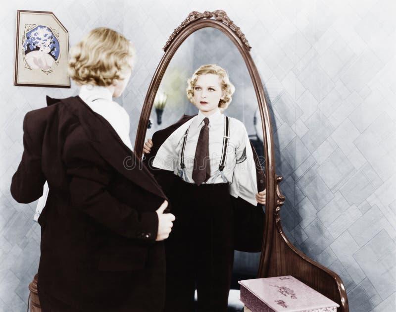 Junge Frau in der Kleidung der Männer, die vor einem Spiegel ausgezogen erhält (alle ex Personen dargestellt sind nicht längeres  stockfoto