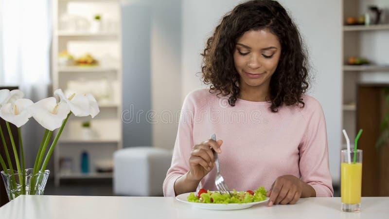 Junge Frau der Mischrasse, die bei Tisch Salat, Gesundheitswesen und das gesunde Nähren isst stockbild