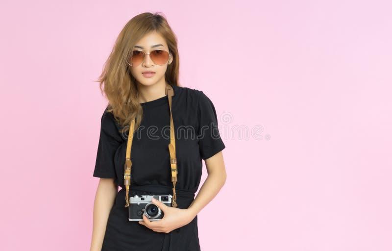 Junge Frau der Mode recht hält Retro- Kamera und tragendes eyewea stockfoto