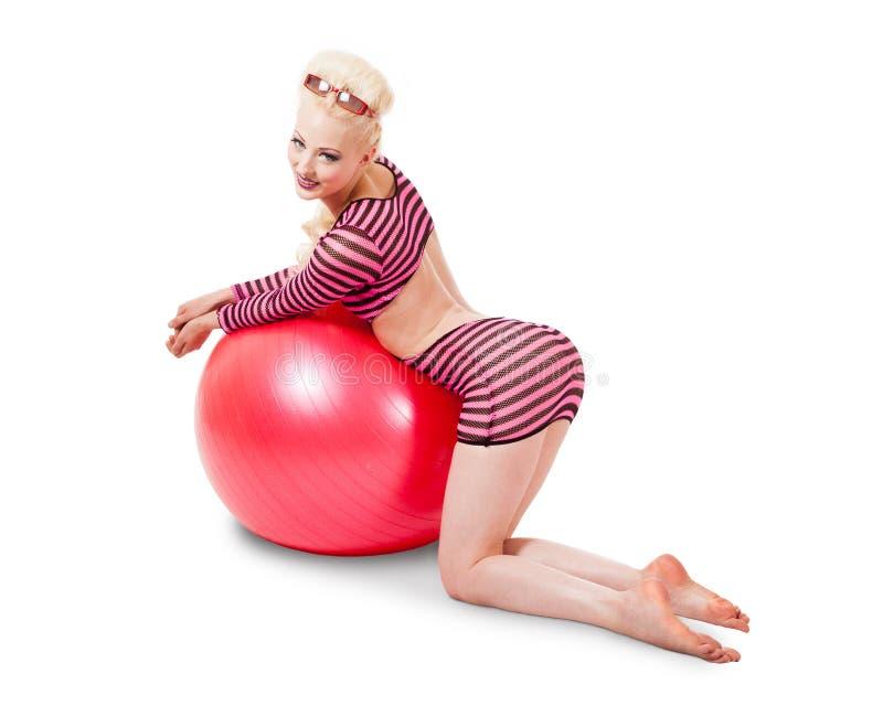 Junge Frau in der modernen Kleidung, die mit Übungsball aufwirft stockbild