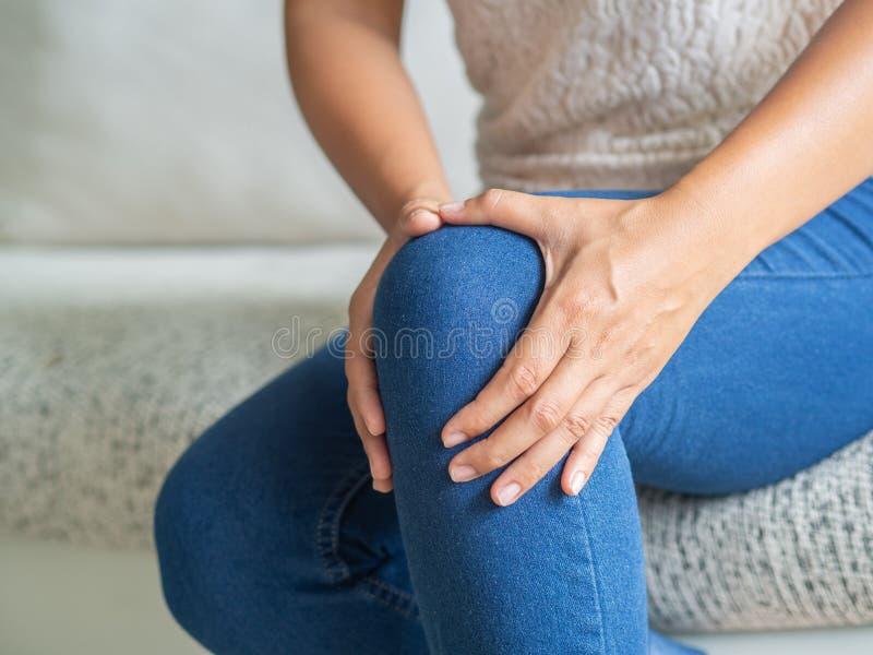 Junge Frau der Nahaufnahme, die auf Sofa und glaubendem Knie sitzt zu schmerzen und SH lizenzfreies stockbild