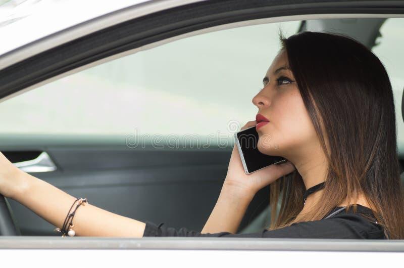 Junge Frau der Nahaufnahme, die im Auto hält die Unterhaltung auf Handy und Kaffeetasse sitzt, wie vom äußeren Treiberfenster ges lizenzfreies stockbild