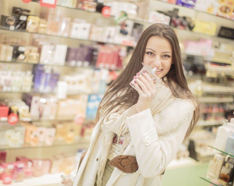 Junge Frau in der Parfümerie stockbild