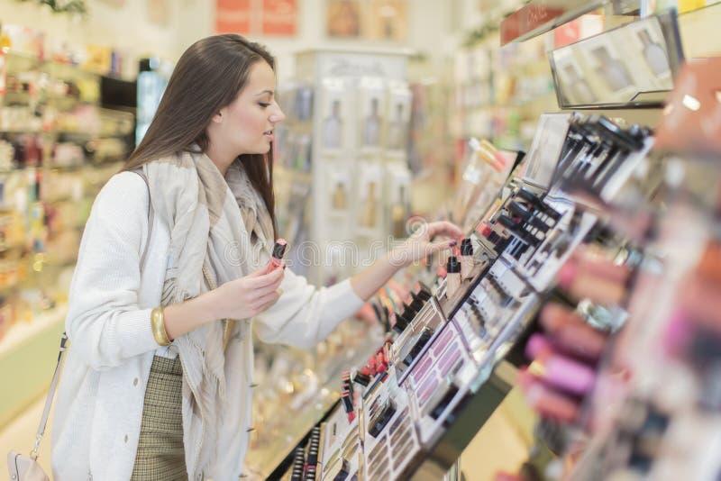 Junge Frau in der Parfümerie stockfotos
