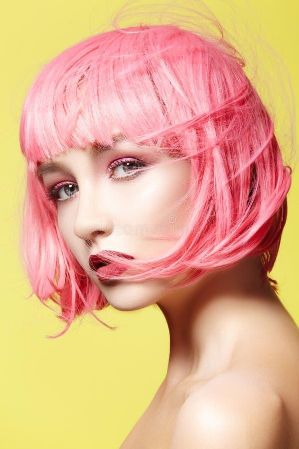 Junge Frau in der rosa Perücke Schönes Modell mit Modemake-up Heller Frühlingsblick Sexy Haarfarbe, mittlere Frisur stockbild