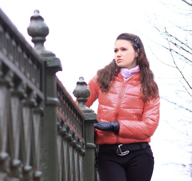 Junge Frau in der roten Herbstjacke auf einem Hintergrund der Stadt lizenzfreie stockbilder