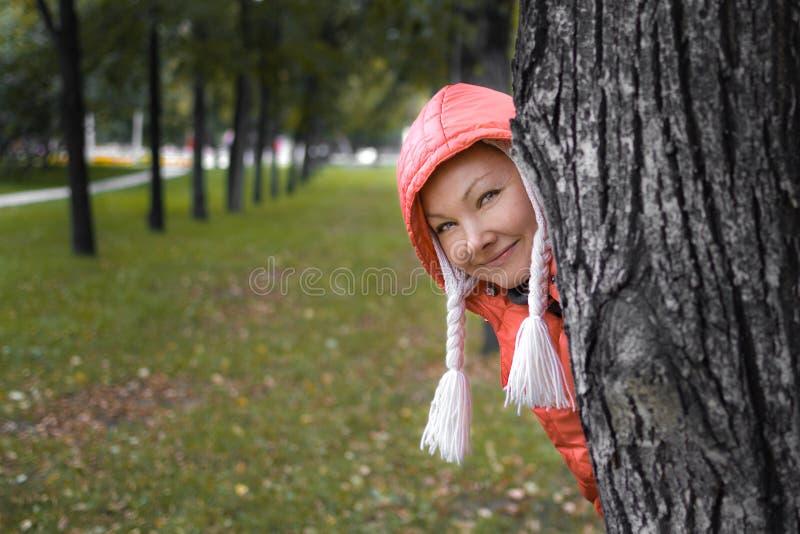 Junge Frau in der roten Jacke schaut heraus stockfotografie