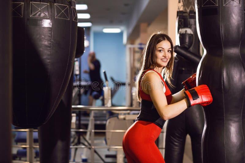 Junge Frau in der roten Sportkleidung und in den Boxhandschuhen, Züge mit einer boxenden Birne in einer dunklen Turnhalle stockbild