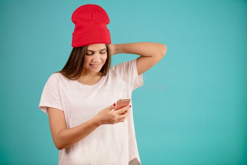 Junge Frau in der roten Strickmütze steht mit Mobiltelefon lizenzfreie stockfotos