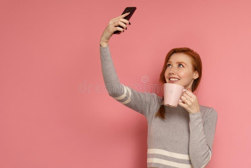 Junge Frau der Rothaarigen lächelt und täuscht vor, für ein selfie zu trinken lizenzfreies stockbild