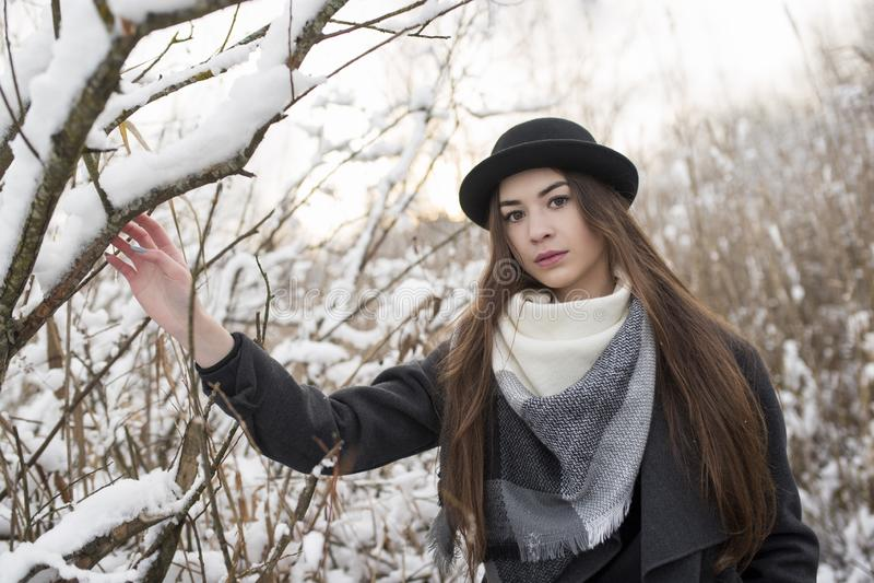 Junge Frau in der schönen Winterlandschaft, mit Schal und Melone an Verwelkte hohe Grasabdeckung durch Schnee lizenzfreies stockfoto