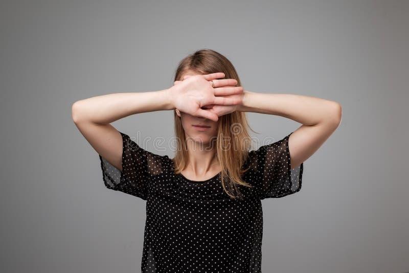 Junge Frau in der schwarzen Kleidung versteckt ihr Gesicht stockfotografie