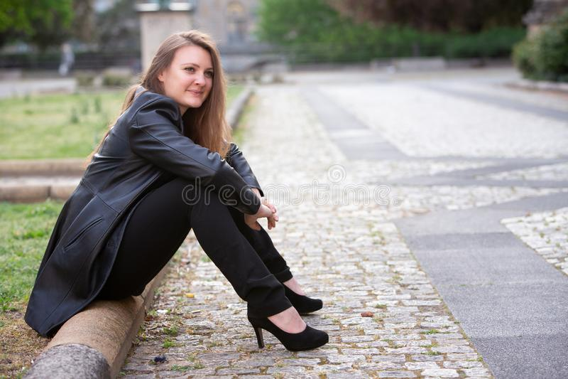 Junge Frau in der schwarzen Lederjacke, die draußen im Park sitzt stockbilder