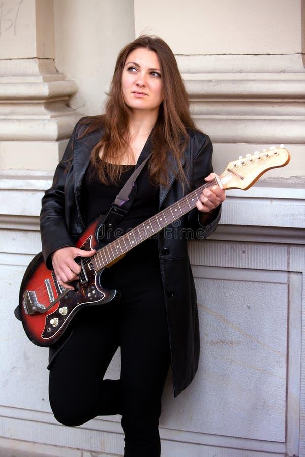 Junge Frau in der schwarzen Lederjacke, welche die Gitarre spielt lizenzfreie stockbilder