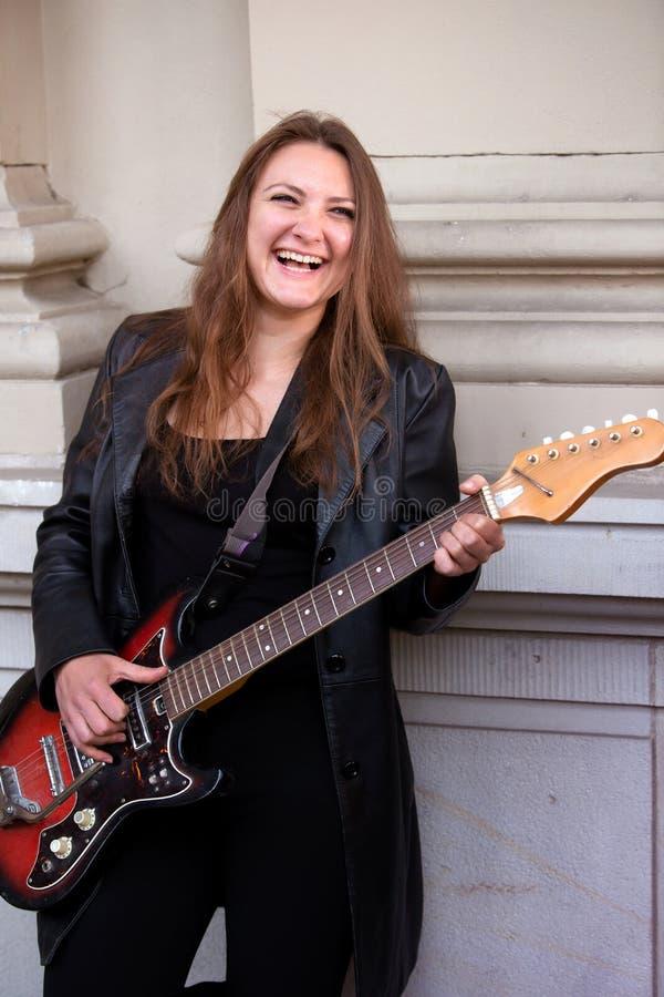 Junge Frau in der schwarzen Lederjacke, welche die Gitarre spielt stockfotos