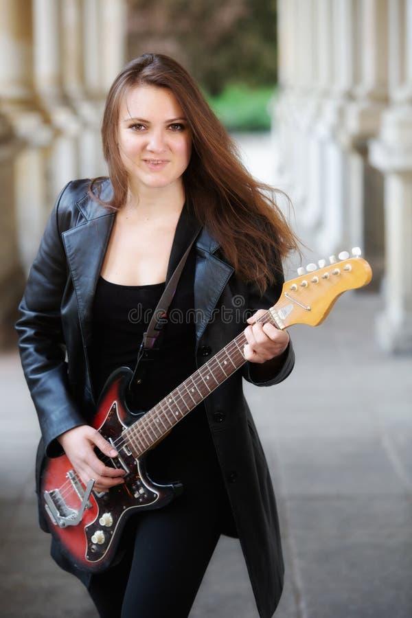 Junge Frau in der schwarzen Lederjacke, welche drau?en die Gitarre spielt stockbild