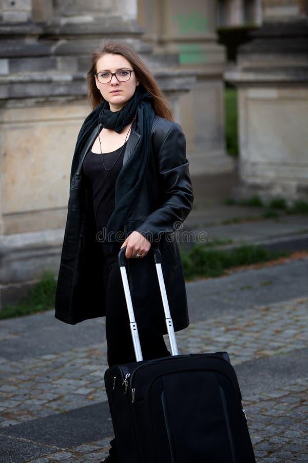 Junge Frau in der schwarzen Lederjackestellung in der Straße mit Koffer stockbilder