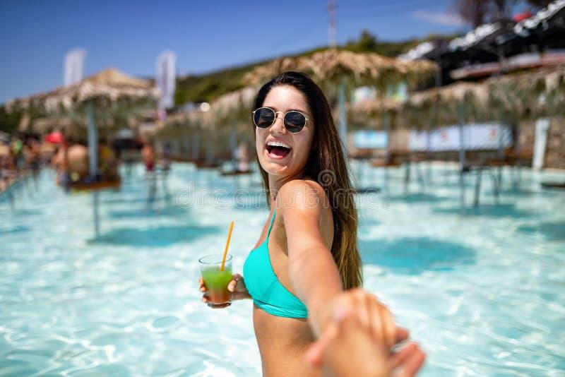 Junge Frau der Sommerferien, die Spaß hat und auf dem Strand im Bikini mit Cocktail lächelt stockfoto
