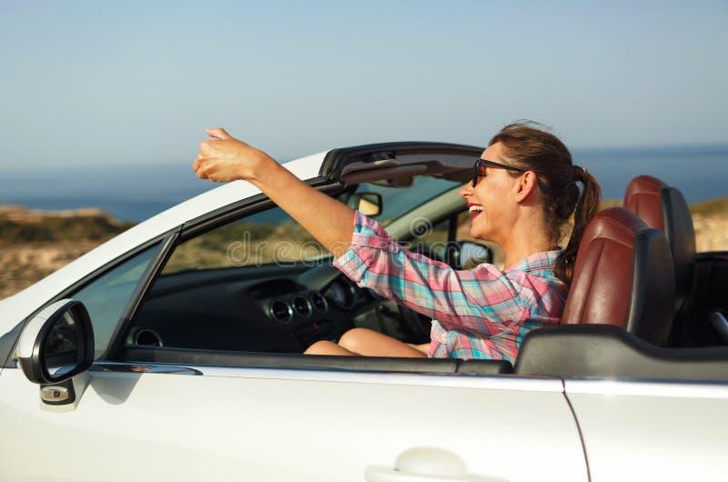 Junge Frau in der Sonnenbrille, die das Selbstporträt sitzt im Auto macht stockfoto